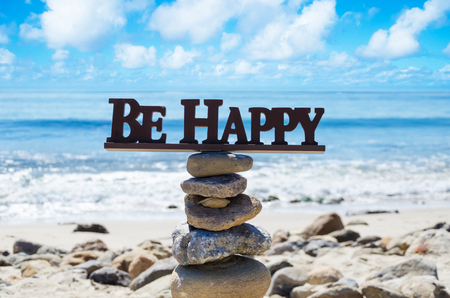 Sign Be happy on the top of rocks balancing by Pacific ocean photo
