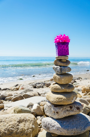 Gift box on the top of sea rocks balancing by Pacific ocean photo