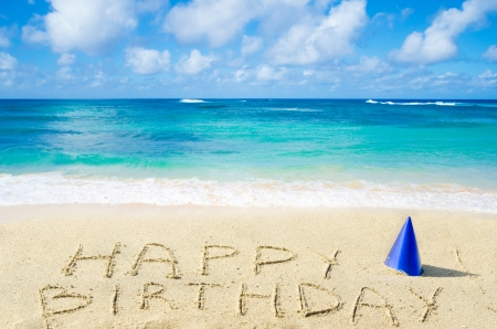 happy holidays text: Sign Happy Birthday with hat on the sandy beach by the ocean