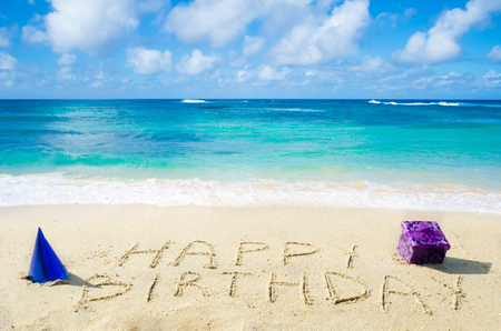 text box: Sign Happy Birthday with decoration on the sandy beach by the ocean