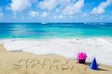 """Teken """"Happy Birthday"""" met decoratie op het zandstrand aan de oceaan"""