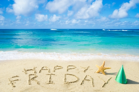 happy holidays text: Sign Happy Friday on the sandy beach by the ocean Stock Photo