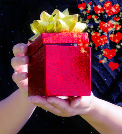 red gift box: Red Gift box with hearts and stars in womans hands