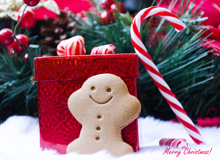 Gingerbread man by the gift box with candy photo
