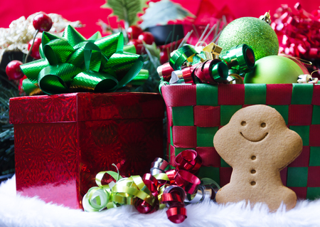 Gingerbread man by the gift box with ribbon and christmas balls photo