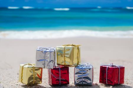 Paar kerstcadeau vak op het zandstrand aan de oceaan Stockfoto