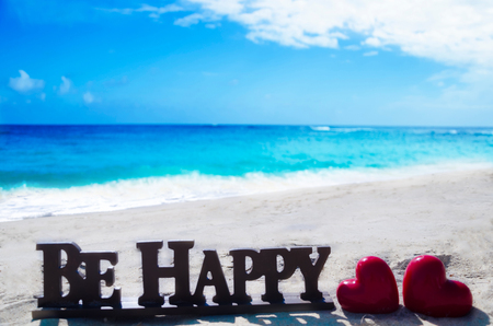Sign Be happy with two heart shapes on the sandy beach by the ocean photo