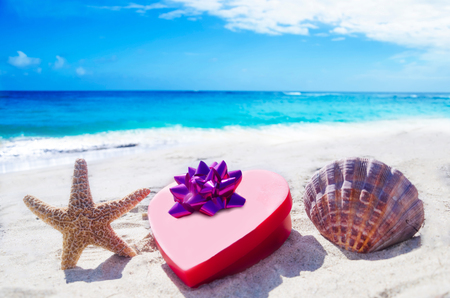Starfish and seashell with heart  on the sandy beach by the ocean photo