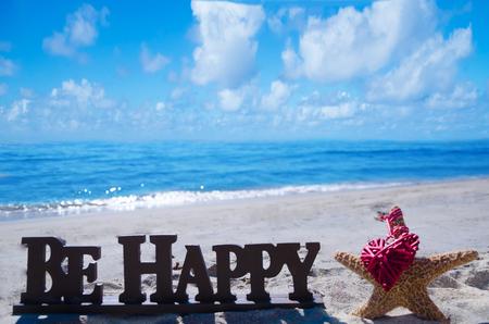"""Anmeldung """"Be happy"""" mit Seesternen und Herz auf dem Sandstrand am Meer"""