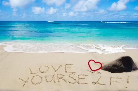 """Ondertekenen """"Hou van jezelf"""" met hart op het strand door de oceaan"""