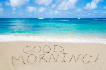 good: Sign Good morning on the sandy beach by the ocean Stock Photo