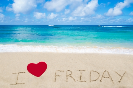 Sign I love Friday with heart on the sandy beach by the ocean