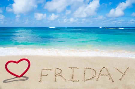 Sign Friday with heart on the sandy beach by the ocean