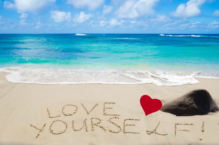 Sign Love yourself with heart on the sandy beach by the ocean Stock Photo
