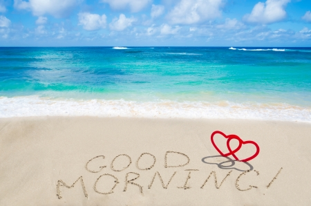 Sign Good morning with two hearts on the sandy beach by the ocean