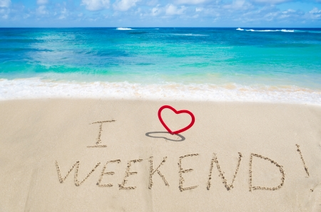 Sign I love weekend with heart on the sandy beach by the ocean