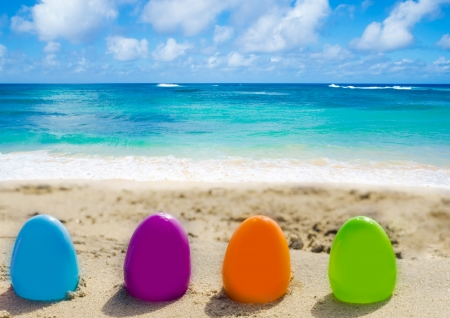 Four color Easter eggs on the sandy beach by the ocean Stock Photo