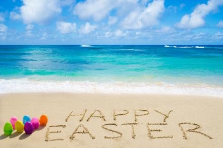 """Ondertekenen """"Vrolijk Pasen"""" met kleureneieren op het zandstrand aan de oceaan Stockfoto"""