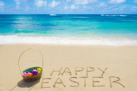 easter sign: Sign Happy Easter with basket and eggs on the sandy beach by the ocean