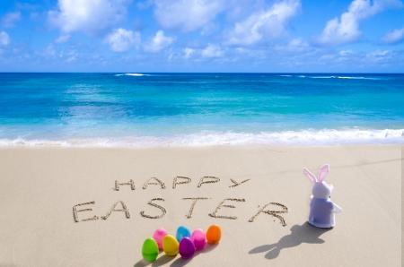 """pascuas navide�as: Firmar """"Feliz Pascua"""" con el conejito y los huevos de colores en la playa de arena junto al mar Foto de archivo"""