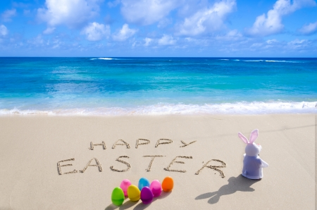 Sign Happy Easter with bunny and color eggs on the sandy beach by the ocean