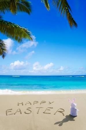 """Sign """"Happy Easter"""" with bunny on the sandy beach by the ocean"""