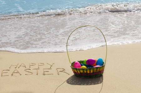 Sign Happy Easter with basket and eggs on the sandy beach by the ocean