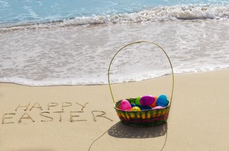 """Teken """"Vrolijk Pasen"""" met mand en eieren op het strand aan de oceaan"""