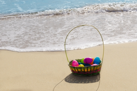 Easter basket with eggs on the sandy beach by the ocean photo