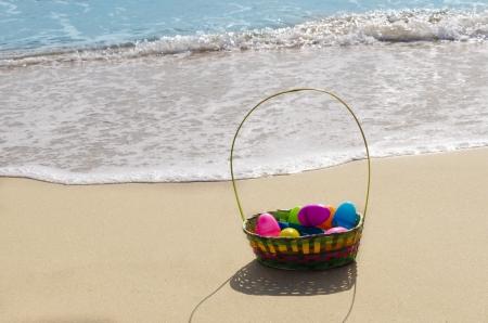 Pasen-mand met eieren op het zandstrand door de oceaan