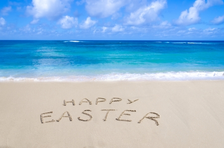 Sign Happy Easter on the sandy beach by the ocean Stock Photo