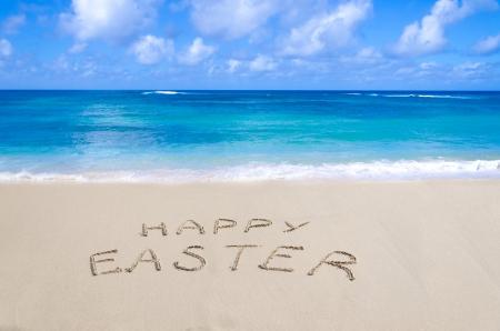 """Teken """"Happy Easter"""" op het zandstrand aan de oceaan"""