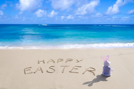 Sign Happy Easter with bunny on the sandy beach by the ocean Stock Photo