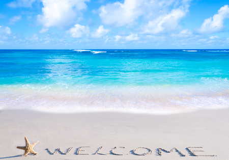 SignWelcome with starfish on the sandy beach by the ocean Banco de Imagens