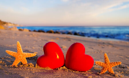 Two Starfishes with hearts on the sandy beach by the ocean photo