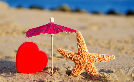 Starfish with cocktail umbrella and heart on the sandy beach by the ocean Stock Photo