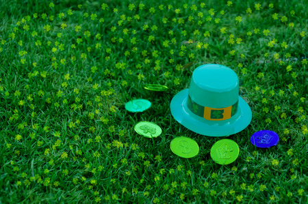 march 17th: St Patricks Day hat and coins on the green grass