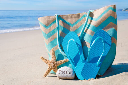Beach bag with starfish, flip flops and rock by the ocean