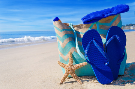 Beach bag with starfish, flip flops and towel by the ocean photo