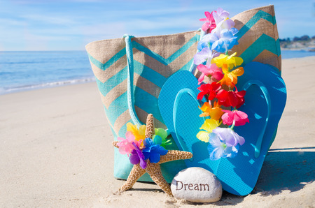 Beach bag with starfish, flip flops and rock by the ocean Stock Photo - 26043182