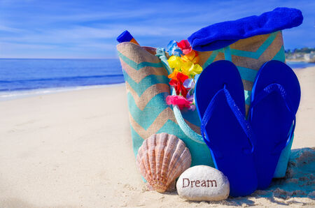 Beach bag with seashell, flip flops, rock and sunscreen by the ocean photo