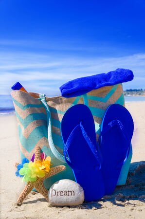 Beach bag with starfish, flip flops, rock and sunscreen by the ocean photo