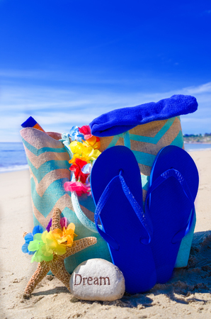 Beach bag with starfish, flip flops and rock by the ocean photo