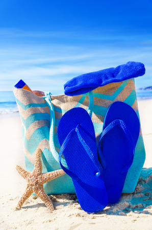 Beach bag with flip flops, starfish and towel by the ocean photo