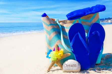 Beach bag with flip flops, starfish, rock and towel by the ocean photo
