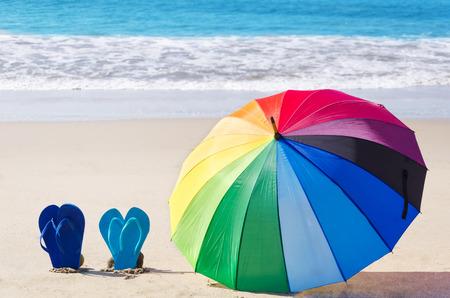 rainbow umbrella: Summer background with rainbow umbrella and flip flops on the sandy beach