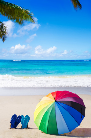 Summer background with rainbow umbrella and flip flops on the sandy beach photo