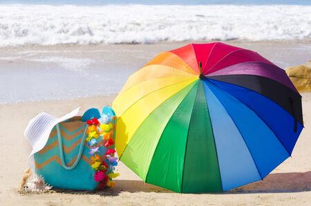 rainbow umbrella: Summer background with rainbow umbrella, white hat and bag on the sandy beach Stock Photo