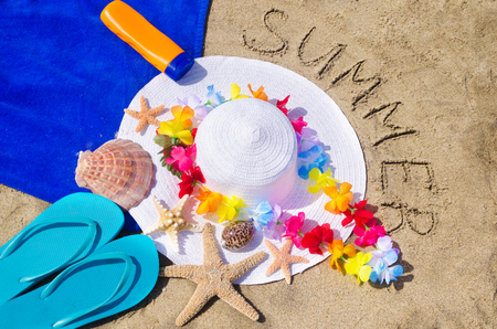 womans white hat with starfishes, seashells, towel, decoration, flip flops and sign Summer on the sandy beach photo