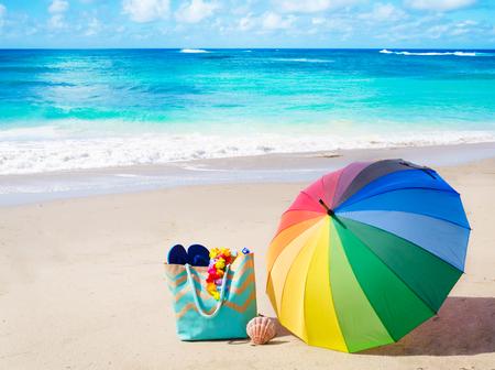 rainbow umbrella: Summer background with rainbow umbrella and bag on the sandy beach